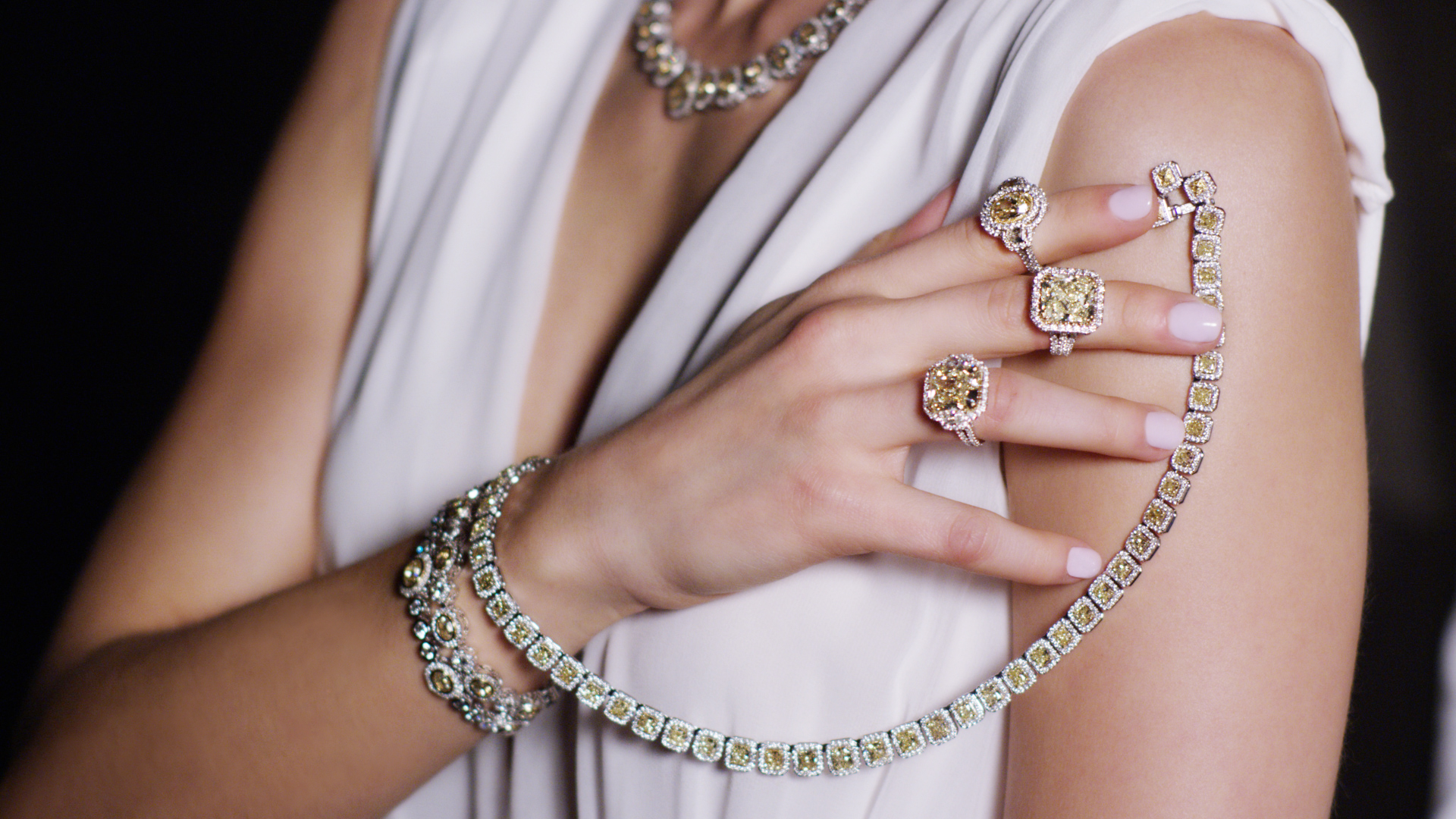 image of a woman holding several karats of white and yellow diamond rings, necklace and bracelet